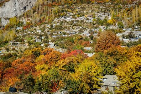 Local village settlement surrounded by colorful foliage forest trees in autumn season in Hunza valley. Gilgit Baltistan, Pakistan. Foto de archivo - 132108559