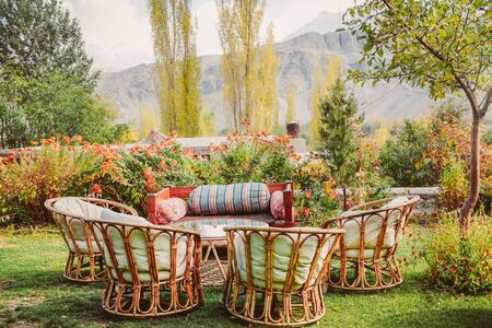 Eco living style garden with local wooden furniture surrounded by beautiful flowers and trees in Shigar. Gilgit Baltistan, Pakistan.
