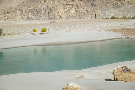 Clear water of Shyok River flowing along the sand beach in Ghanche. Gilgit Baltistan, Pakistan.