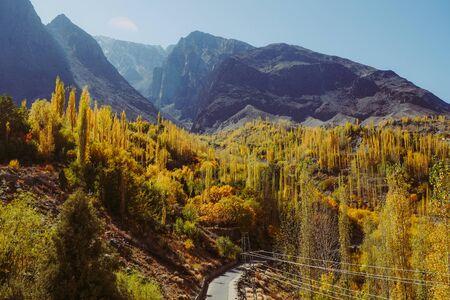 Beautiful landscape view of Gupis valley. Colorful trees in autumn season against Hindu Kush mountain range. Gilgit Baltistan, Pakistan.