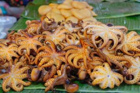 Grilled Dollfus Octopus on banana leaves for sale in local street food fresh market. Bangkok, Thailand.