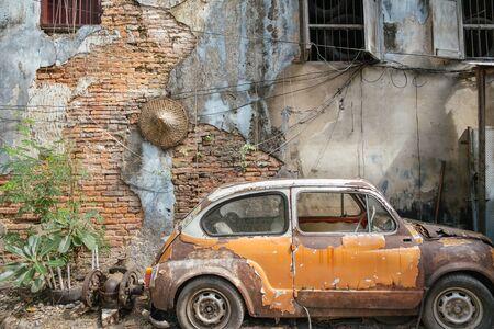 Bangkok,Thailand. November 30,2019 : Abandoned wrecked orange vintage car against old brick wall background.