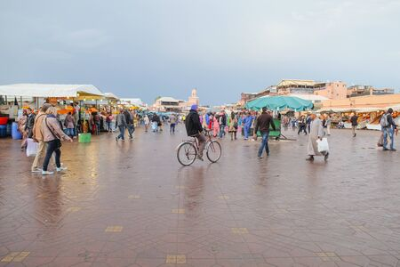Medina Marrakech,Morocco. March 12,2014 : Tourists and local pedestrian people walking and cycling around the old street market for shopping and sightseeing at Djemaa el-Fna square.