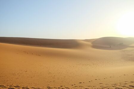 Hot weather in Erg Chebbi sand dunes against clear blue sky background in Sahara desert. Merzouga, Morocco.