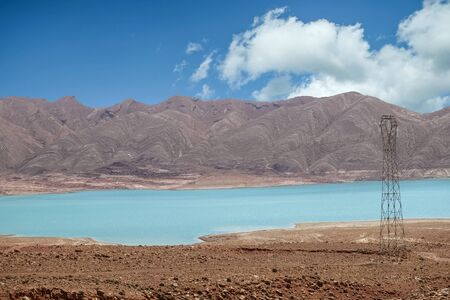 Blue water of a Moroccan reservoir against mountain and sky in rural Morocco. Banque d'images