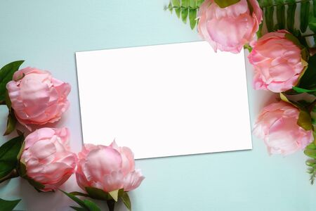 Top view of pink Peonies artificial flowers on light blue background with  blank white note paper