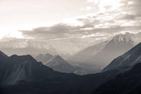 Nature aerial landscape view black and white photo of sunrise over snow capped Karakoram mountain range with morning fog in Nagar valley. Gilgit Baltistan, Pakistan.