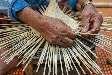 Hands of old artisan craftsman elderly working weaving rattan and bamboo to make ancient handmade handcraft wicker traditional Thai wooden hat Banque d'images