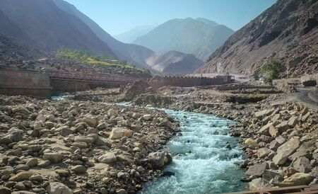 Flowing fresh clean blue green water of river along Karakoram highway and mountain range in the background. Peaceful landscape view of Gilgit Baltistan in summer for nature tourism, Pakistan.
