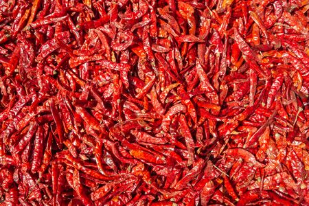 Texture background and pattern of cultivated dried red hot chili peppers with Capsaicin. Top view local organic product, outdoor natural sun drying method. Banque d'images