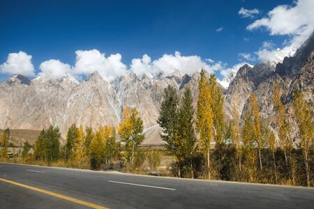 Nature landscape view of clouds cover Passu cones cathedral mountain peaks along paved road in Karakoram highway, Gojal Hunza valley. Gilgit Baltistan, safe and peaceful Pakistan