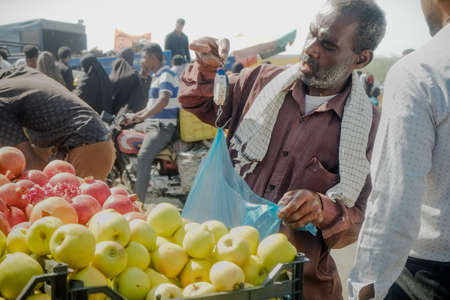 Hormozgan province, Iran. October 27, 2016 : Local Iranian street fruit vendor using manual hanging weighing scale to sell goods on his small business at Minab Thursday fresh market
