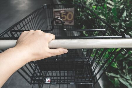 Asian hand holding shopping cart handle, risk to contaminated with germs virus bacteria and pathogen. Covid-19 disease coronavirus outbreak concept