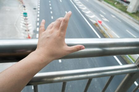 Asian hand touching footbridge railing handrail, risk to contaminated with germs virus bacteria and pathogen. Covid-19 disease coronavirus outbreak concept