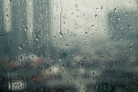 Closeup raindrops water droplets trickling down on wet clear window glass during heavy rain against blurred city view in rainy day monsoon season