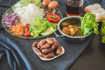 Top view flat lay iftar and sahoor meal serving on dining wooden table at Muslim family home in kitchen during fasting holy month. Ramadan halal food, Ramadan Kareem and eid al fitr concept