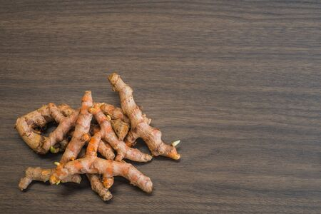 Pile of fresh organic turmeric curcuma root on wooden background with copy space. Food cooking ingredient spice or use for natural yellow fabric dye raw material Banque d'images