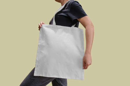 Woman holding reusable white cotton linen eco organic fabric tote bag isolated blank background for mockup with clipping path Banque d'images