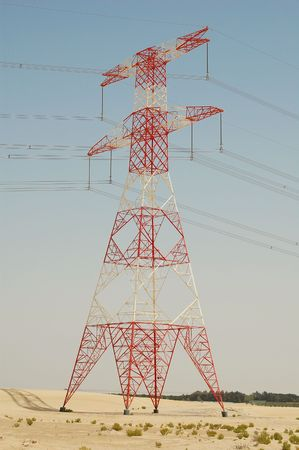 Pole of high voltage (400kV) transmission line straddled in a desert. Painted in red and white be easier recongnized by pilots. photo
