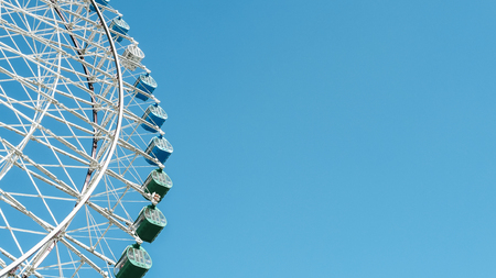 Large ferris wheel revolves around a circle with a blue sky as the background. Stock Photo