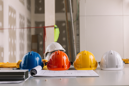 Yellow,white, Blue, Orange helmet safety engineer for project engineering.On the floor of the desk.