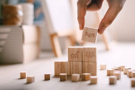 Close up hand of businessman arranging wood cube stacking as step stair. Business growth icons. Alternative risk concept, Investment plans and strategies. Stok Fotoğraf