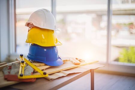 Concept of engineer and safety, White safety helmet and Yellow and blue overlaid on the table with overlapping wood craft equipment for the worker safety project in the building. Banque d'images