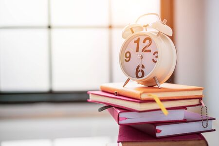 Education background and back to school concepts.Close up white clock on top of books stacked on a wooden table. Copy space. 免版税图像
