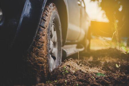 Les pneus de voiture en gros plan sont sales sur la boue. Pendant la saison des pluies, aventure en plein air et voyage. Banque d'images