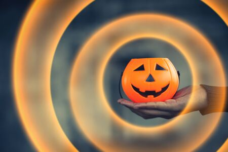 Pumpkin carved smiling face holding a protruding front with black background, Jack O Lantern Halloween.