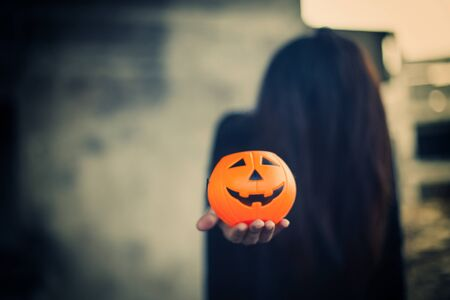 Jack O Lantern Halloween. Pumpkin carved smiling face holding a protruding front with a woman ghost  background. Stok Fotoğraf