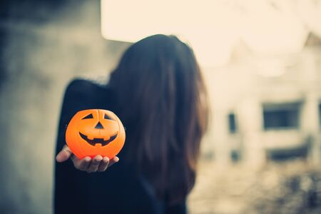 Pumpkin carved smiling face holding a protruding front with a woman ghost  background, Jack O Lantern Halloween.