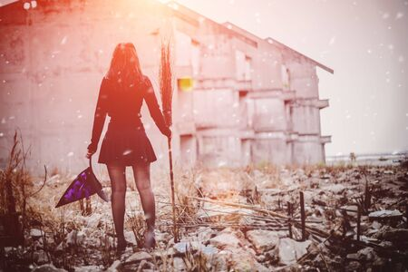 Halloween concept. Horror theme. Young witch in a black dress stands holding a broom along with the abandoned building background.