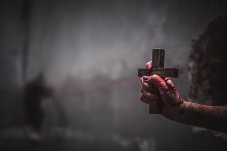 Close up bloody hands holding the crucifix of Jesus on a black background, Symbol of belief and christian religion.