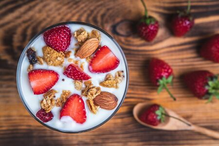 Health concept - Yogurt and strawberries on a wooden table, Homemade granola. Top view. Stok Fotoğraf