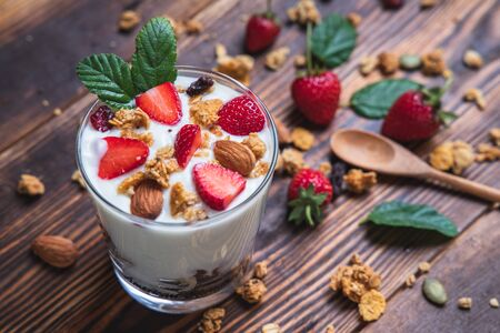 Top view bowl of homemade granola and yogurt mixed with fresh strawberries on a wooden table along with almonds on the side. Stok Fotoğraf