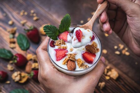 Health concept - Top view hands holding a spoon, yogurt and strawberry on a wooden table.