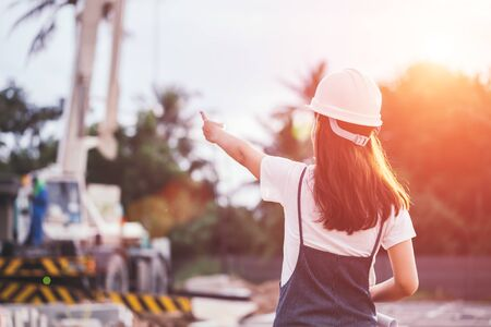 Portrait of engineer woman looking for construction, Asian female architect with blueprints standing on the background of construction work, Engineering and architecture concept.