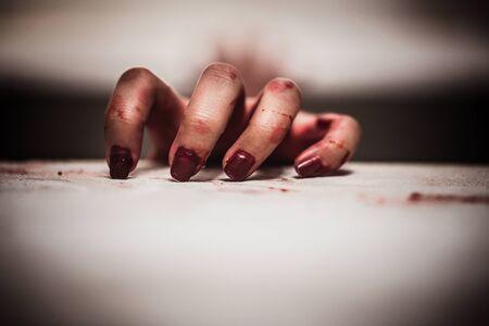 Blutige Hände im Dunkeln, Nahaufnahme einer Hand, die sich schmerzhaft und einsam anfühlt und an Depressionen leidet. Horror-Thema.
