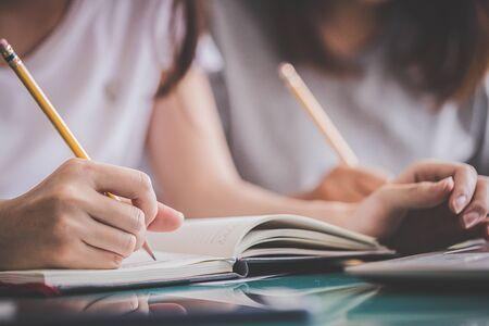 Educación y concepto de regreso a la escuela: primer plano de la mano de un estudiante sosteniendo un lápiz o bolígrafo para escribir en el cuaderno el día del examen final.