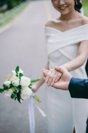 Close-up image of the groom holding the brides hand with the ring on the hand. Romantic young couples enjoy the morning sun on the wedding day.