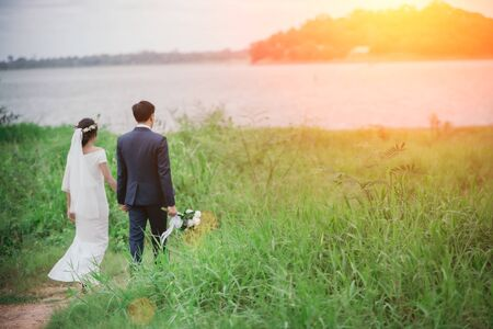 Couples in romantic wedding dresses are enjoying a stroll through the beautiful sunset with a green grass background. Warm love on valentines day.