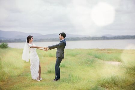 Marriage or valentines day concept - The groom and the bride dressed in white are dancing on the green fields on his wedding day. Young lovers are walking hand in hand in the garden.