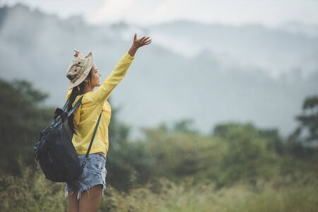 Camping concept - Happy woman standing arms outstretched and relax life on a natural mountain view after rain. Hiking on holidays in Asia enjoy traveling during the rainy season.