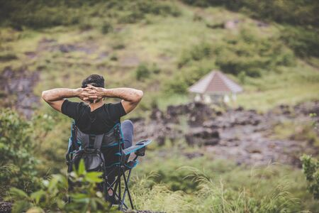 Camping in the middle of nature mountains with fresh air. Young man sat in a relaxing chair on his vacation.