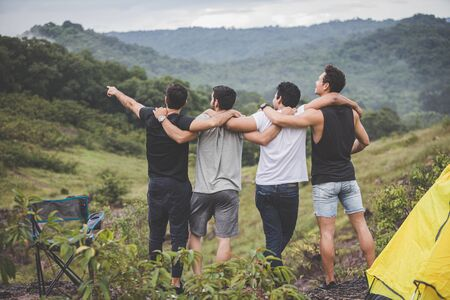 Camping in the middle of nature mountains with fresh air. Group of young men stood to watch the nature happily and joyfully in the spring.