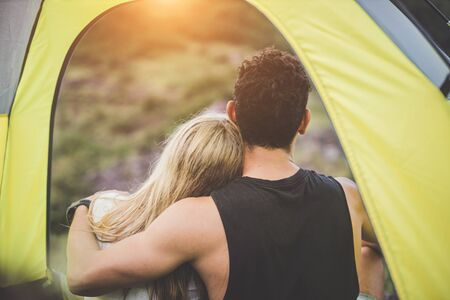Couple camping lovers hug other with love in the tent. Two people watching the view of the mountain in a relaxing holiday.
