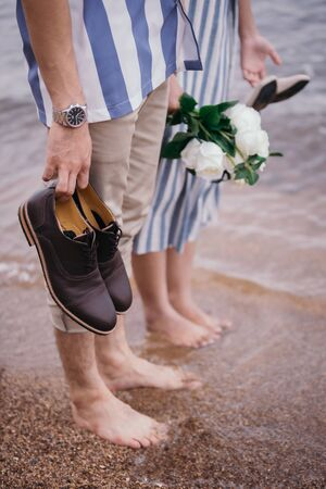Close-up photos of a bouquet of flowers and shoes, the groom and the bride, placed on the sandy beach with ocean waves as the evening sunset background. Reklamní fotografie