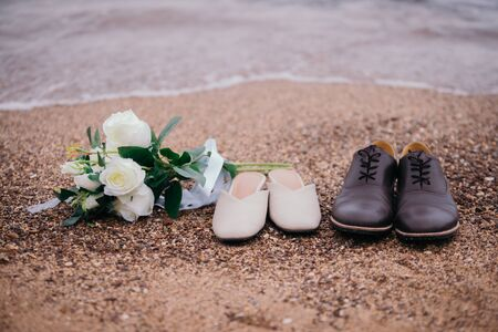 Close-up photos of a bouquet of flowers and shoes, the groom and the bride, placed on the sandy beach with ocean waves as the evening sunset background. Stok Fotoğraf