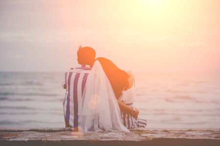 Rear view of a happy couple sitting embrace and lean on the shoulder the beach watching the sunset in summer. Men and women with love are showing through the body by embracing. Stok Fotoğraf